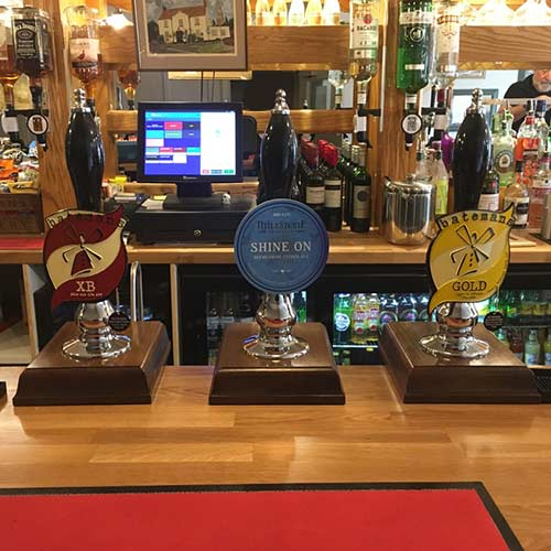 Three real ale pumps on a bar
