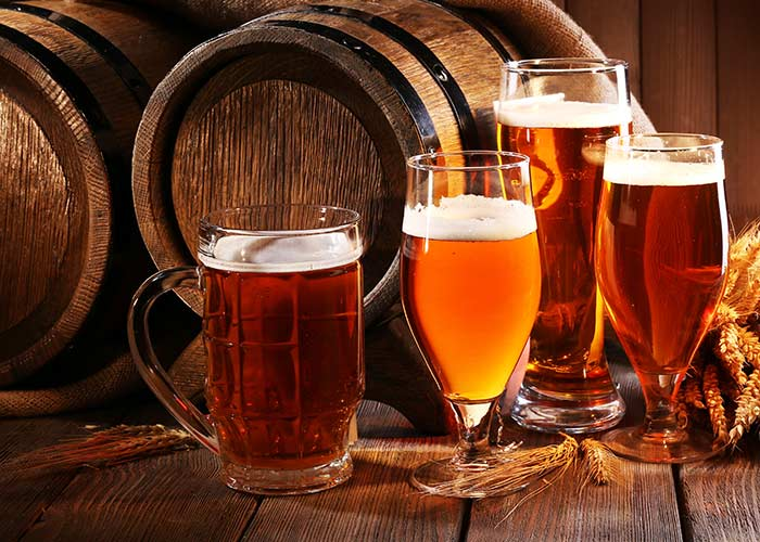 A range of beers in front of two wooden barrels